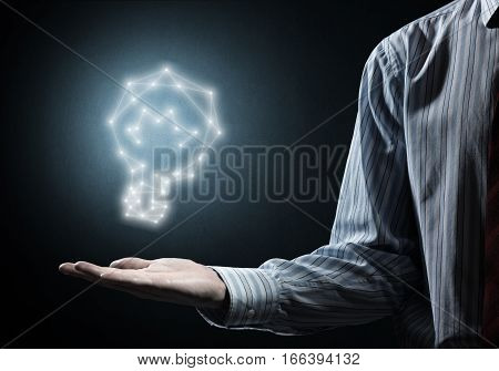 Close up of businessman hand holding glowing bulb sign in palm