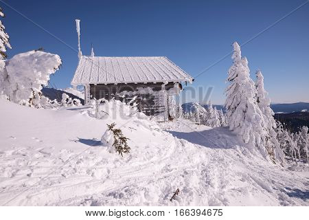 Mountain wooden huts covered with frozen snow. Grosser Arber Bayerisch Eisenstein Germany. Winter snowy summit of Mt. Grosser Arber at Bavarian Forest (Germany).