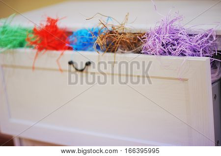 A drawer filled with colourful raffia for handmade and design gifts for the holidays blur close-up.