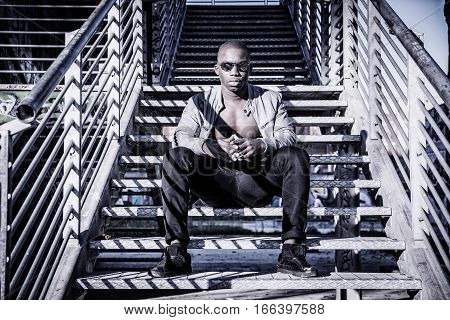 Portrait of a hot black man in sunglasses with visible abs posing for camera in urban setting, with leather jacket on naked torso, sitting