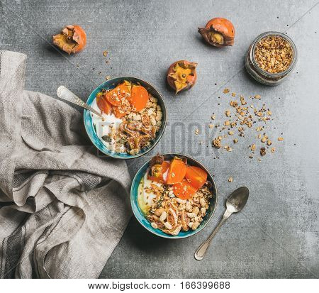 Healthy vegetarian breakfast. Oatmeal, quinoa granola with yogurt, dried fruit, seeds, honey, persimmon in bowls over grey background, top view. Gluten free, slow food, allergy-friendly concept