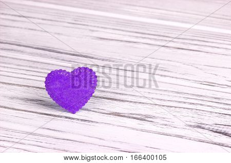 Purple heart of felt on a white wooden background. Valentine Day.Greeting card.Wedding
