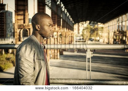 Portrait of a sexy young black man in urban environment wearing red shirt and grey leather jacket