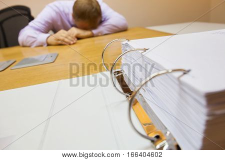 Young business man with problems and stress in the office sitting in front of the folder stock photo selective focus