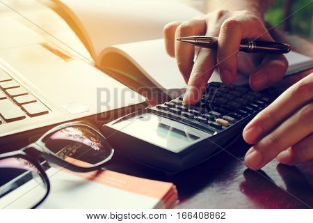 Close Up Man Calculate Cost On Desk At Home.