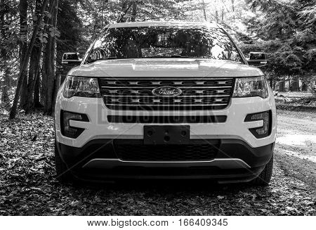 Pocono Lake, Pennsylvania, July 7, 2016: A white 2016 Ford Explorer parked by a dirt road in a forest.