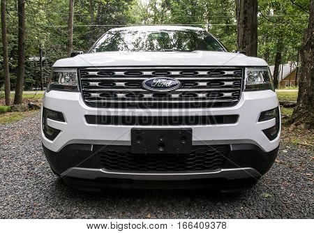 Pocono Lake, Pennsylvania, July 7, 2016: A frontal view of a 2016 Ford Explorer parked in a gravel driveway.