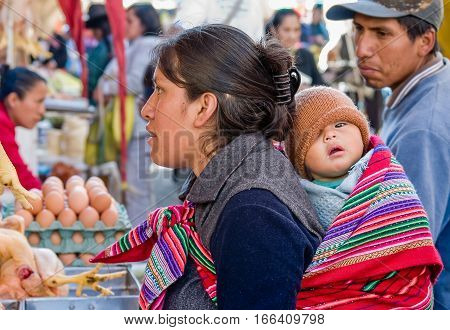 Peru, August 14, 2007: A mother carrying her child behind her back is shopping on a farm market.