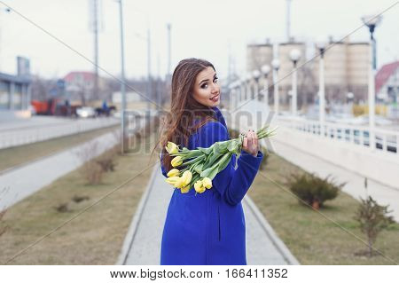 Young attractive girl in a blue coat and yellow dress holding a bouquet of yellow tulips. Spring is coming to town. She walks down the sidewalk and turned back