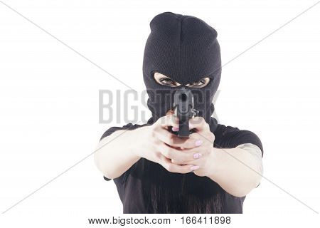 Aggressive woman with a black balaclava pointing to camera with a pistol. Isolated over a white background. Shallow depth of field focus on her eyes.
