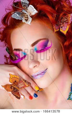 Beautiful young red haired woman with bright colorful makeup covered with butterflies over purple background. Portrait beauty shot.