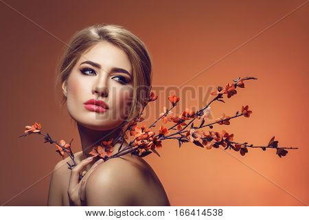 Beautiful young woman with make-up and loose hairdo with artificial sakura branch with orange flowers. Beauty shot on brown background. Copy space. poster