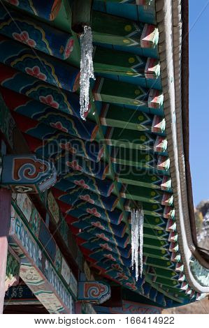 Close up of the hand painted wooden eaves and beams of the roof of the Buddhist Arayabal Meditation Temple in Gorkhi-Terelj National Park in Mongolia. The colorful art has geometric and floral designs. Icicles hang from the eaves.