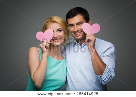 Beautiful young couple holding big pink hearts. Blond woman in mint dress and handsome man in shirt and trousers standing on grey background. Valentine's day concept. People in love. Copy space.