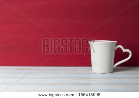 White mug with heart handle in front red grunge background on white table. Valentines concept.