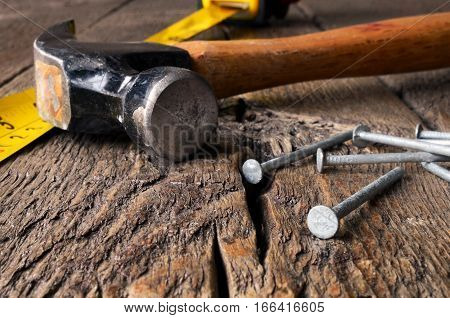 A close up image of an old wooden hammer and several nails on a workbench.