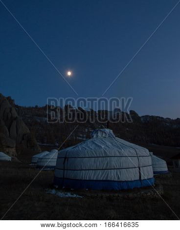 Several white and blue canvas yurts in the moon light. The background shows the outline of the rugged mountains. Photographed in Mongolia.