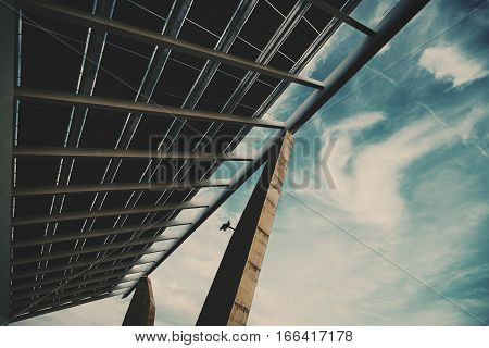 Wide angle view from bottom of modern hi-tech solar photovoltaic panel with empty space for your message on the right huge solar battery giant energy producing structure Barcelona Spain