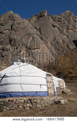 Close up of two white and blue canvas yurts or gers with paneled wooden doors and stone foundations at the base of rugged stone mountains. Photographed in Mongolia.