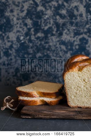 Sliced homemade brioche on a dark background. Front view. Delicious pastries