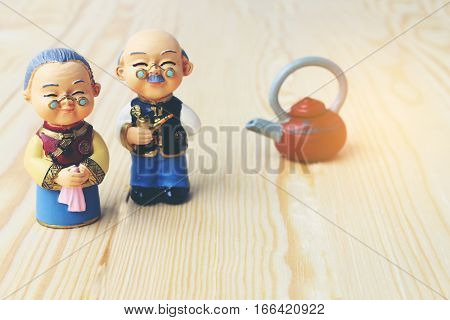 Grandma And Grandpa Dolls In Chinese Uniform Style Standing On Wooden Background. In Chinese New Yea