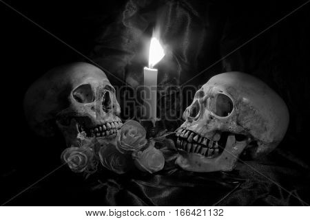 Skull With Bunch Of Flowers And Candle Light On Wooden Table With Black Background In Night Time In