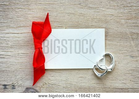 Valentine's day empty white paper label red ribbon two silver hearts on a wooden board
