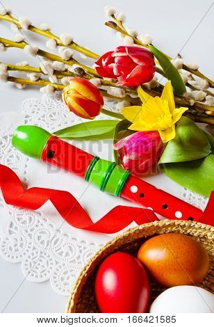 Traditional Czech easter decoration - my handmade painted eggs with daffodils tulip and pussycats flower and wooden music instrument flute. Spring easter holiday arrangement.