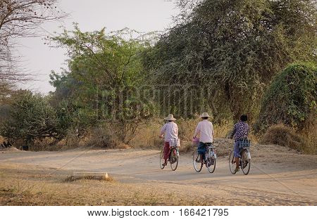 Burmese People Biking On Rural Road In Bagan
