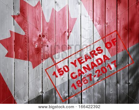 150 years of Canada 1867-2017 red stamp words on wooden background with Canadian flag