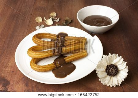 Churros, traditional Spanish, especially Madrid, dessert, often for Sunday breakfast, in the form of horseshoe, with a bowl of chocolate on a wooden board texture