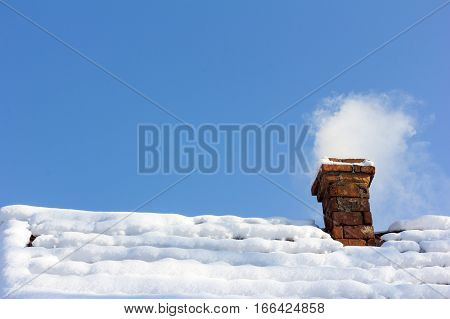smoke out of a brick chimney on a snowy rooftop on the background of blue sky