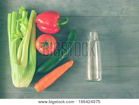 Group of vegetables tomato pepper celery carrots cucumber beets to prepare fresh juice on grey wood background. Horizontal arrangement top view. Tinted glass