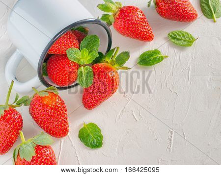 Fresh red strawberries in metal cup. Strawberry in rustic cup on oriental white background. Top view or flat lay