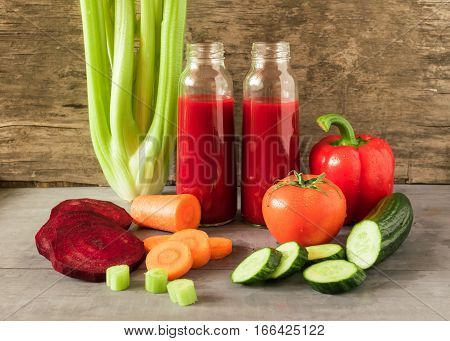 Fresh juice from vegetables tomato pepper celery carrots cucumber beets poured into small glass bottles which stand side by side on grey wooden table. Horizontal arrangement front view.