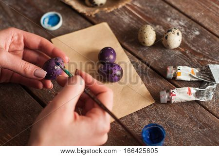 Close up of hands coloring eggs. Man preparing for Easter, handmade decoration of must have attribute of holiday. Art, hobby, tradition concept