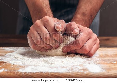 Male hands kneading dough close-up. Baker man preparing pastry for bread, homemade recipe. Profession, bakery, culinary concept