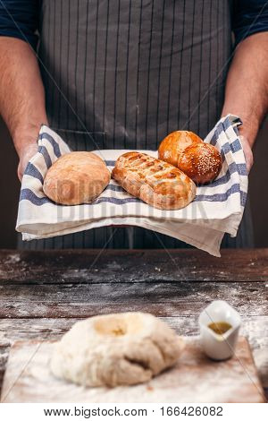 Man holding warm crusty bread above dough free space. Unrecognizable baker standing with made bread near raw pastry, presentation of new recipe, homemade bakery concept