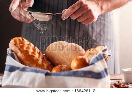 Unrecognizable baker finishing his pastry close-up. Man sprinkling fresh crusty bread with flour, final step. Traditional rustic recipe, homemade bakery, cooking process concept