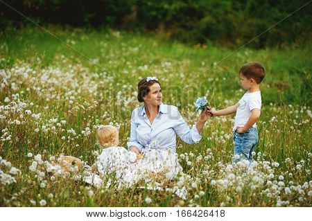young mother playing with children in nature