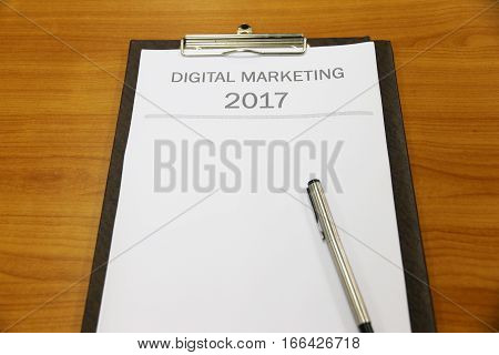 Digital Marketing for 2017 papers on table in office room.
