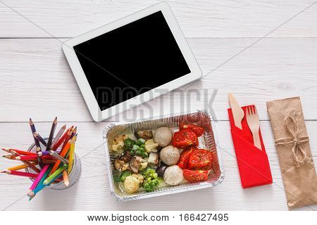 Healthy lunch and diet concept. Take away food in foil box, tablet with copy space and pencils on table of creative person, designer or school student. Meat with vegetables, top view on white wood