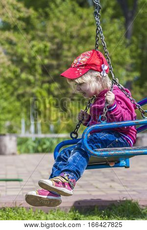 Cute little girl on a swing. Smiling child playing outdoors in autumn.