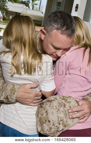 Young girl hugging her father in uniform.
