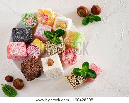 Turkish delight on white rustic background. Turkish deligh set. Assorted traditional turkish delight on oriental background poster