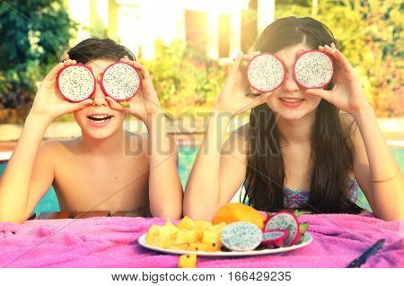 teen boy and girl with dragon fruit circles on swimming pool background