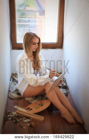 Beautiful woman in a shirt and underwear draws paints on the floor near the window.