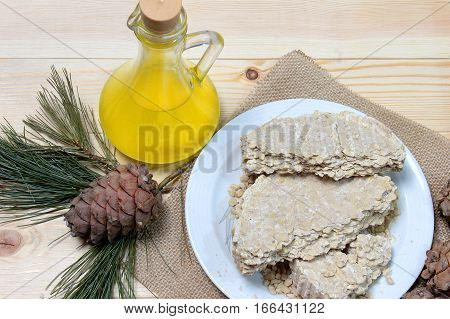 Food for vegans. The cedar oil in a glass bottle with cedar oil cake on the plate, next to a pinecone with pine branch decorations. Template for advertising eco store.