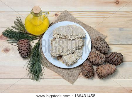 Food for vegans. The cedar oil in a glass bottle with cedar oil cake on the plate, next to a pinecone with pine branch decorations. The view from the top.