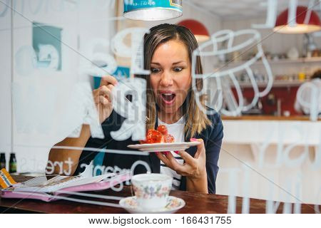 Portrait of astonished brunette eating strawberry cake in cafe.From behind the window